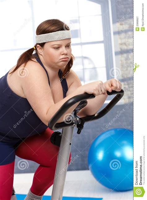 Exhausted Fat Woman On Exercise Bike Royalty Free Stock